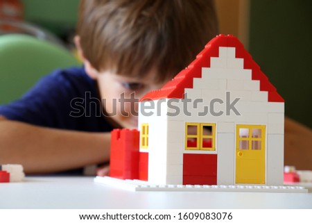 Boy builds a house with building blocks  #1609083076