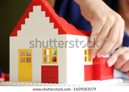 Boy builds a house with building blocks  #1609083079