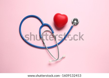 Modern stethoscope and red heart on color background #1609132453