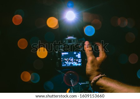 A photograph taken in night showcasing techniques of long exposure and blur/bokeh effect. A camera, a bike, a cellphone, and two friends in a dark and high altitude place with a view of the city. #1609153660