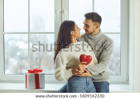 Valentine's day. Beautiful smiling couple gives a heart on a background of a window in a room #1609162330