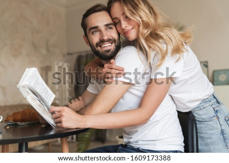 Cropped image of a lovely smiling young couple embracing while sitting at the table in kitchen, reading book #1609173388