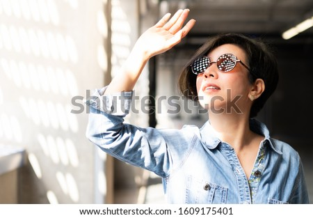 Beautiful / Stylish Asian woman wearing 100% UV light eyes protection sunglasses, stand and raise her hand to block out bright glare and sunlight from outside to avoid ultraviolet rays over exposure.  Royalty-Free Stock Photo #1609175401