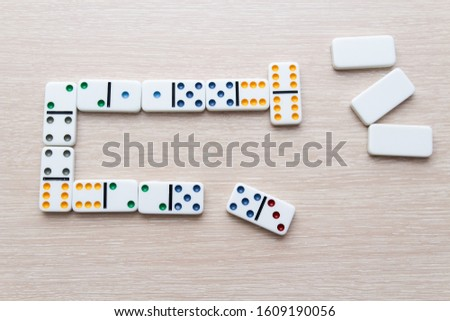 white Domino dice on a light wooden table, the process of playing dominoes #1609190056