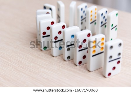 white dominoes stand in a row on a light surface, close-up #1609190068