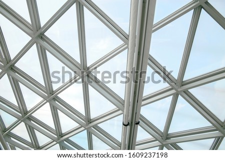 Glass wall or roof panels of structural glazing. Close-up of minimalist business building interior. Abstract modern architecture background. Hi-tech geometric structure of triangular windows pattern. #1609237198