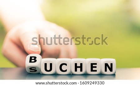 """Hand turns a dice and changes the German word """"suchen"""" (""""search"""" in English) to """"buchen"""" (booking"""" in English). #1609249330"""