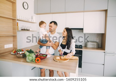 Family in a kitchen. Beautiful mother with little son. Father in a white t-shirt. #1609255105