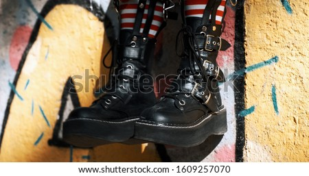 Goth teenager girl slide with rough boots striped stockings sits on ornate wall of an abandoned building. Alternative in youth. An alternative in youth. Hipster, freak, emo, grunge. Copy