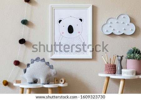Stylish scandinavian nursery interior with mock up photo frame, plush dino, design furniture, toys and accessories. Beautiful decoration on the beige background wall. Home decor for children room.
