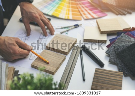 designer choosing flooring and furniture materials from samples for home interior design project Royalty-Free Stock Photo #1609331017