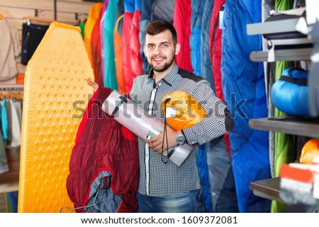 Young cheerful  man choosing touristic equipment in sports equipment store  #1609372081