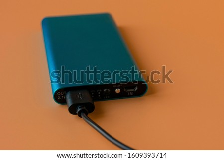 Power bank for charging mobile devices and devices. Blue smartphone charger with power bank. External battery for wireless headphones and speakers on an orange background.
