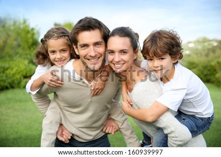 Parents giving piggyback ride to children #160939997