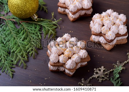 Honey star cakes with cream topped with golden sugar on the wooden table. Festive dessert #1609410871