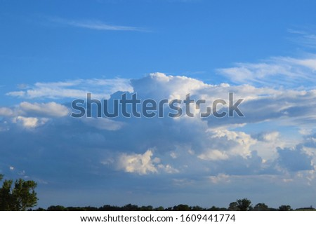 Big cloudscape over a sunny summer farm field #1609441774