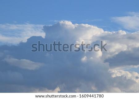 Big cloudscape over a sunny summer farm field #1609441780
