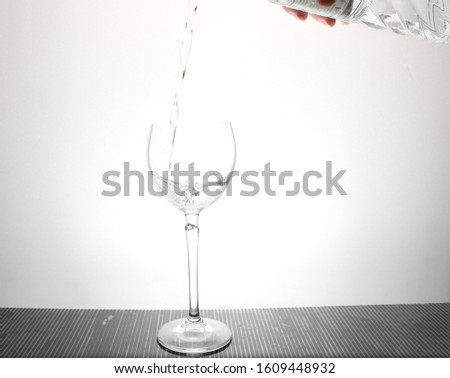 puring water from bottle into wine glass #1609448932