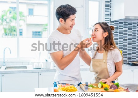 Asian boyfriend feeding fruit and vegetable to girlfriend to each other during preparing for dinner in home kitchen. Couple and Family concept. Honeymoon and Holidays. Man and woman cooking happily #1609451554