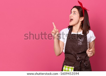 Picture of good looking funny chef being in high spirits, feeling inspiration for new dishes, making gesture with forefinger, holding whisk, opening mouth widely in shock. Copyspace for advertisement.