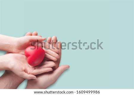 Hands holding a red heart on pastel background #1609499986