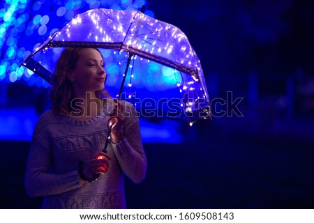Girl in the rain with an umbrella with lights and creative lighting.Horizontal photo
