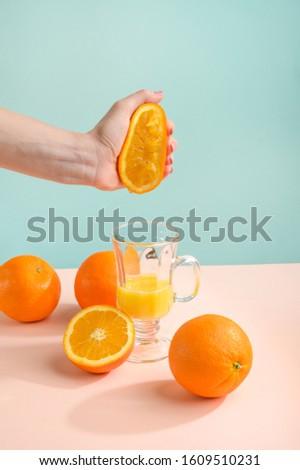 Creative and fashionable photo, pastel colors. Female hand crushes orange, juice. #1609510231