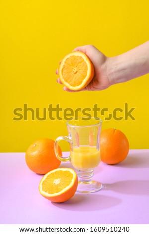 Female hand holding crushes orange and juice. #1609510240