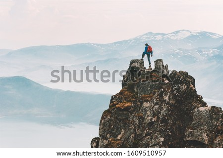Traveler man climbing on mountain top adventure travel extreme healthy lifestyle vacations hiking outdoor success achievement brave hiker on the edge #1609510957