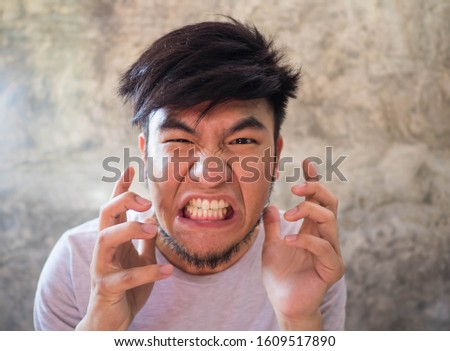 Asian man with a beard wearing a white T-shirt Expressing anger, resentment, anger, and anger, and able to destroy everything that is close to him In a cement backdrop There is space for copy space. #1609517890