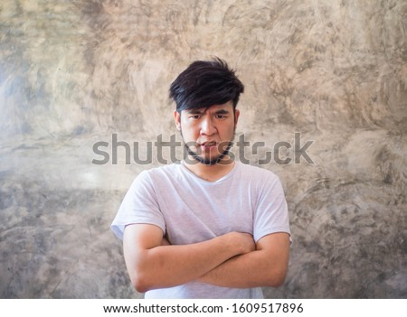 Asian man with a beard wearing a white T-shirt Expressing anger, resentment, anger, and anger, and able to destroy everything that is close to him In a cement backdrop There is space for copy space. #1609517896