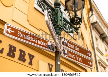 The architecture of the old city of Prague. Street lamp with signs indicating directions to the sights. Prague / Czechia - 05.21.2019 #1609569517