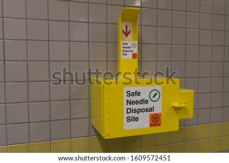 Safe medical needle disposal container on a toilet wall #1609572451