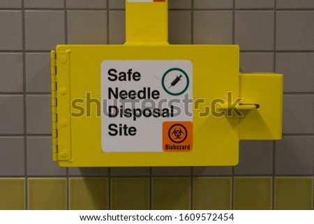 Safe medical needle disposal container on a toilet wall #1609572454