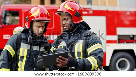 Portrait of two firefighters in fire fighting operation, fireman in protective clothing and helmet using tablet computer in action fighting.  #1609609390