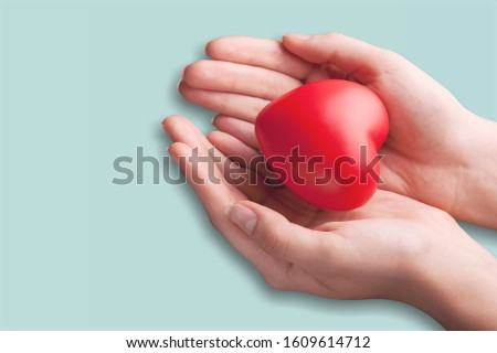 Hands holding a red heart on pastel background #1609614712