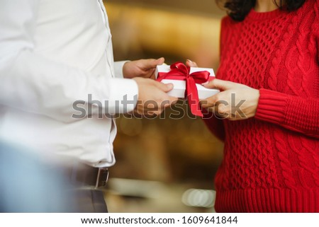 Man gives to his woman a gift box with red ribbon. Hands of man gives surprise gift box for girl. Lovers give each other gifts. Young loving couple celebrating Valentine's Day. Romantic day. #1609641844
