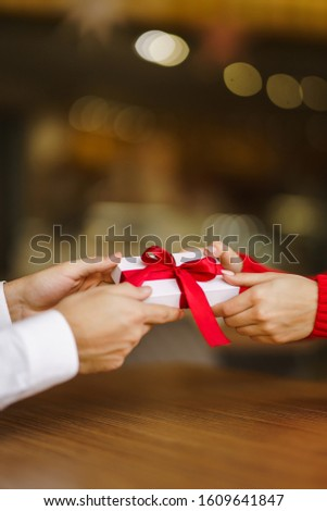 Man gives to his woman a gift box with red ribbon. Hands of man gives surprise gift box for girl. Lovers give each other gifts. Young loving couple celebrating Valentine's Day. Romantic day. #1609641847