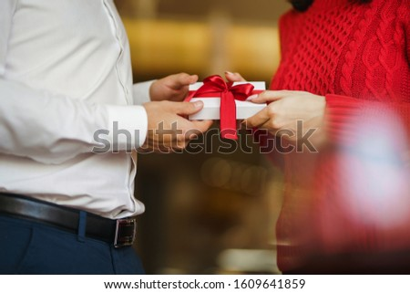 Man gives to his woman a gift box with red ribbon. Hands of man gives surprise gift box for girl. Lovers give each other gifts. Young loving couple celebrating Valentine's Day. Romantic day. #1609641859
