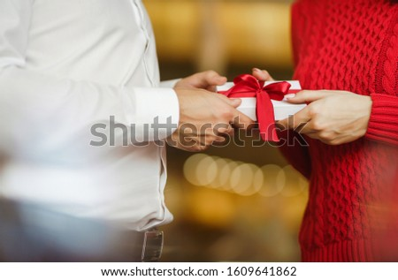 Man gives to his woman a gift box with red ribbon. Hands of man gives surprise gift box for girl. Lovers give each other gifts. Young loving couple celebrating Valentine's Day. Romantic day. #1609641862