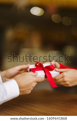 Man gives to his woman a gift box with red ribbon. Hands of man gives surprise gift box for girl. Lovers give each other gifts. Young loving couple celebrating Valentine's Day. Romantic day. #1609641868