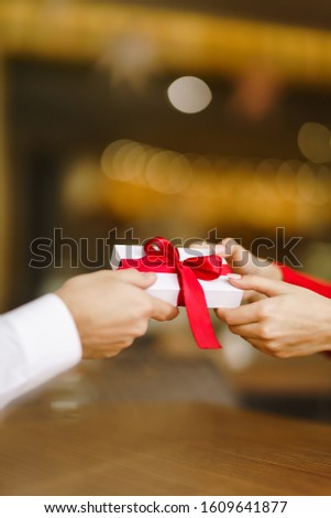 Man gives to his woman a gift box with red ribbon. Hands of man gives surprise gift box for girl. Lovers give each other gifts. Young loving couple celebrating Valentine's Day. Romantic day. #1609641877
