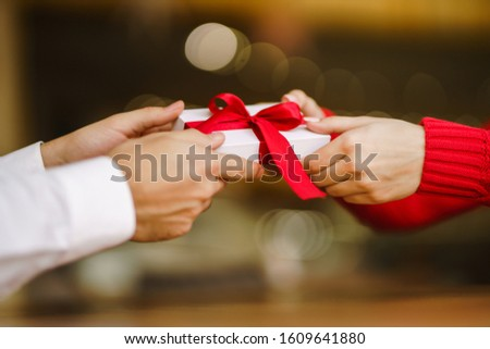 Man gives to his woman a gift box with red ribbon. Hands of man gives surprise gift box for girl. Lovers give each other gifts. Young loving couple celebrating Valentine's Day. Romantic day. #1609641880