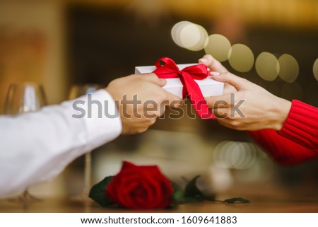 Man gives to his woman a gift box with red ribbon. Hands of man gives surprise gift box for girl. Lovers give each other gifts. Young loving couple celebrating Valentine's Day. Romantic day. #1609641883