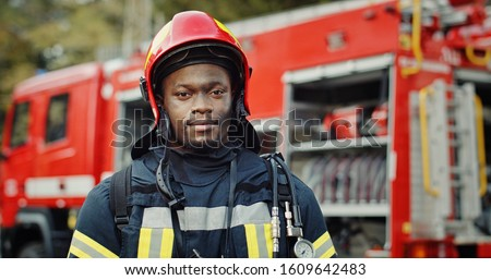 Portrait of african american Firefighter in uniform and helmet near fire engine. #1609642483