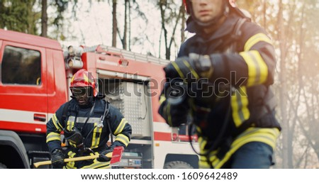 Two firefighters in fire fighting operation, fireman in protective clothing and helmet with equipment in action fighting #1609642489