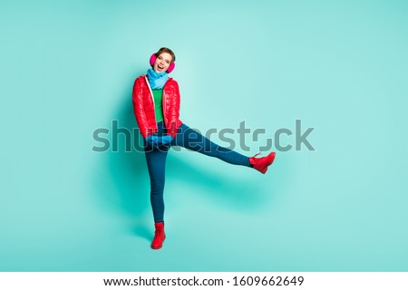 Full length photo of funny lady winter day walk street spend best free time raise leg high wear casual red overcoat scarf gloves pink ear muffs pants shoes isolated teal color background #1609662649