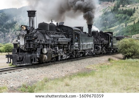 "SILVERTON, COLORADO/USA - JULY 24, 2019: Durango & Silverton Narrow Gauge Railroad train with two steam locomotives, referred to locally as a ""double puffer"", arriving from Durango #1609670359"