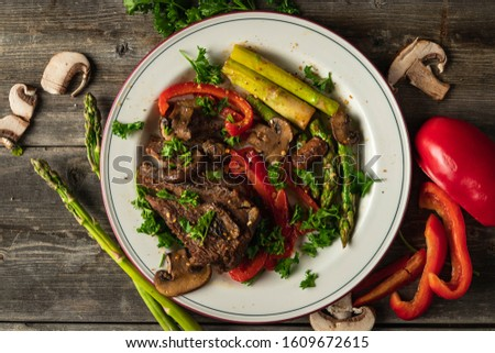 Some juicy and Delicious cooked steak with fresh fried vegetables on a white plate and wood background #1609672615