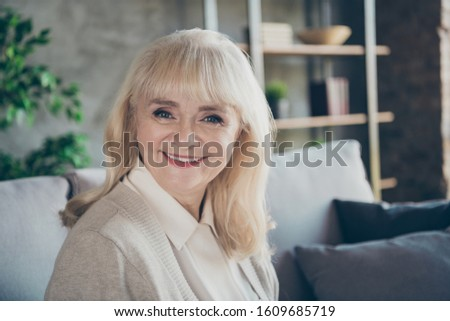Closeup photo of amazing blond adorable aged granny homey good mood toothy beaming smiling cheerful sitting comfort sofa divan living room indoors #1609685719